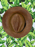 brown panama hat with black band on a banana leaf print background