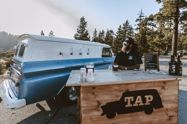 Big Bear custom mobile bar with rustic wooden bartop and baby blue vintage panel truck.