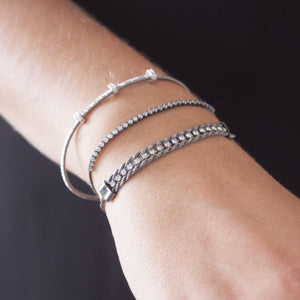 Model wearing black rhodium three rondel and diamond cut bangle stacked with other braclets I Dream Of Silver collection
