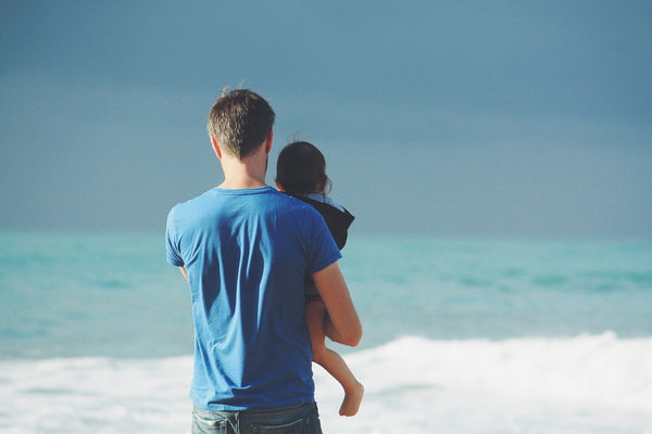 dad holding child beach ocean watching