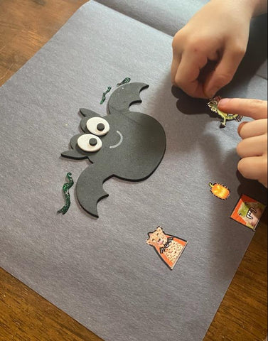 A black piece of construction paper that a child is decorating