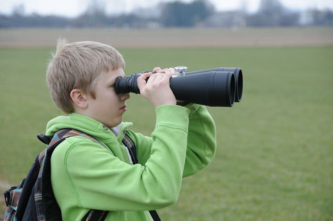 young boy looking through binoculars outside