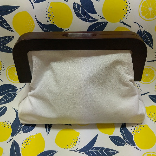 White leather Yellowbird clutch with dark timber handles. Australian made at Spinifex Collections.