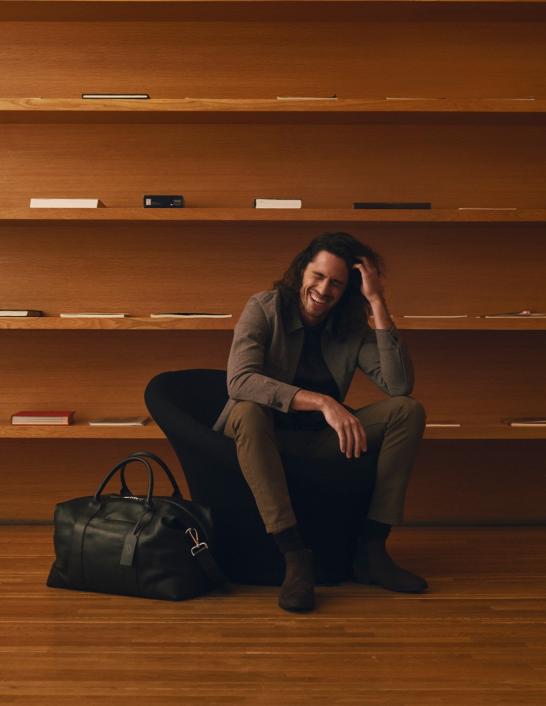 Man sitting in front of book shelves smiling with duffle bag at his feet