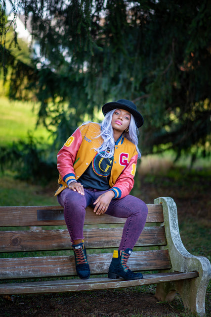 """Black woman sitting on top of a bench in a park. Wearing black Fedora wide brim hat, long gray curly hair, G.A.M.E. varsity jacket, G.A.M.E. swarovski crystal logo on black sweater, red jeans, and G.A.M.E. military boots."""