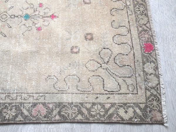 Beige with pink and turquoise accents. Vintage Turkish Rug.