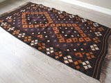 Full view of brown, orange, navy, cream Vintage Turkish Kilim Rug.