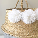 Detail view of pom poms on Kit + Loom silver dipped seagrass belly baskets.