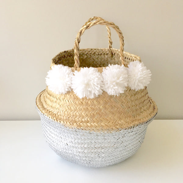 View of small seagrass belly basket from Kit + Loom. Cloud white pom pom detail.
