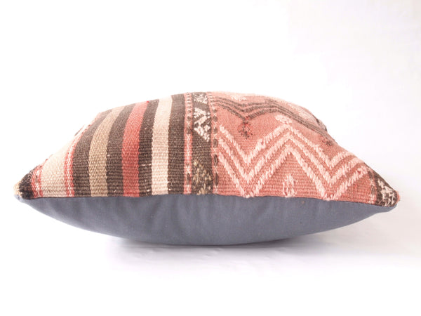 Side view of Turkish Kilim Pillow. Blush and Brown tones.
