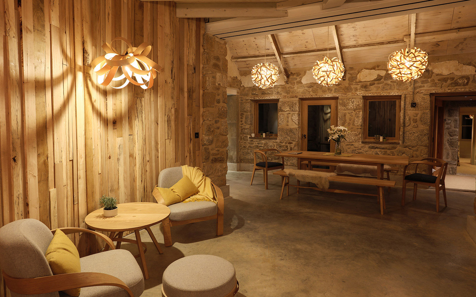 Inside Tom Raffield's house, with wooden walls, concrete floor and his steam-bent-wood lights