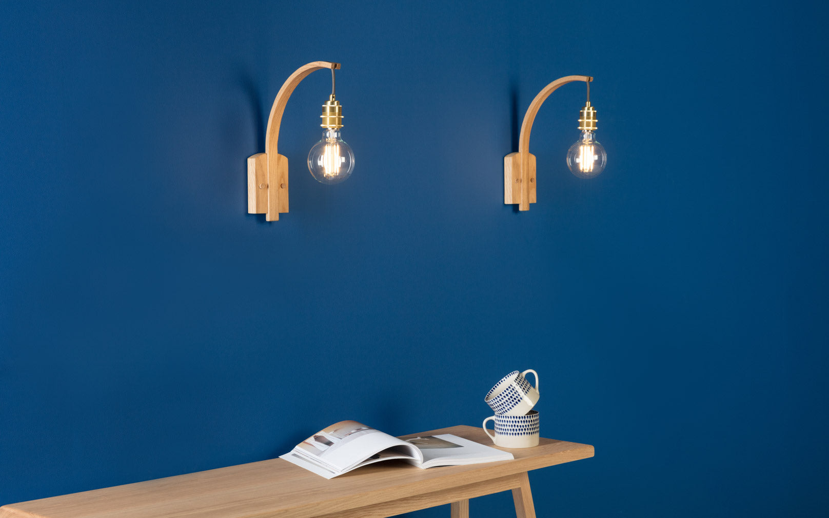 Hanter Wall Lights in Oak make a statement against a regal blue accent wall