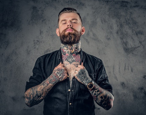 Studio portrait of bearded hipster man with tattoos on his arms, chest and neck