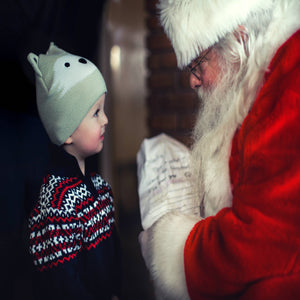 small child and santa with a list More Of You and Photo by Mike Arney