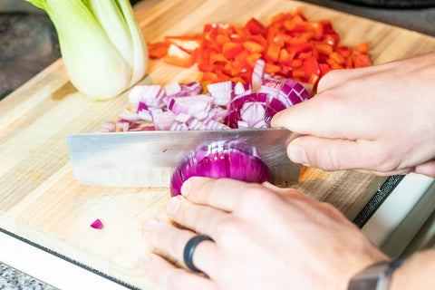 slicing onions and peppers on cutting board
