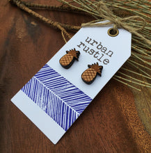 Wooden pineapple stud earrings on rustic wood