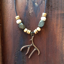 Tribal elk antler necklace on rustic wood