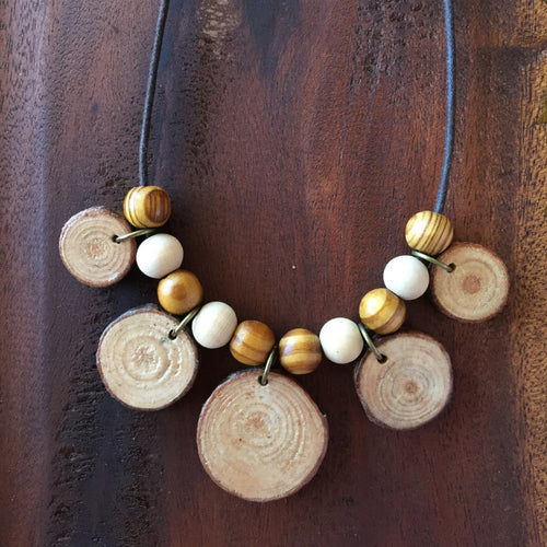 Tree Ring wooden necklace on rustic wood