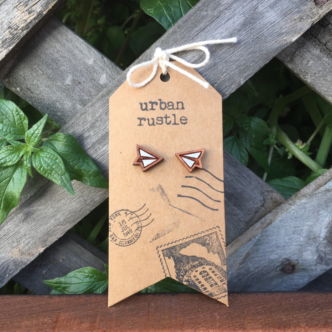 Mini paper plane wooden stud earrings on timber lattice