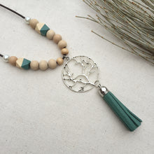 Silver charm and green tassel on wooden beaded necklace