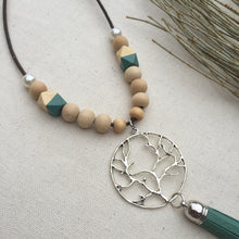 Silver tree-of-life charm detail on wooden beaded necklace