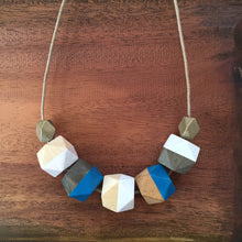 Blue and white wooden beachy geometric necklace on rustic wood