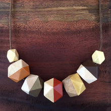 Red orange gold wooden geometric necklace on rustic wood