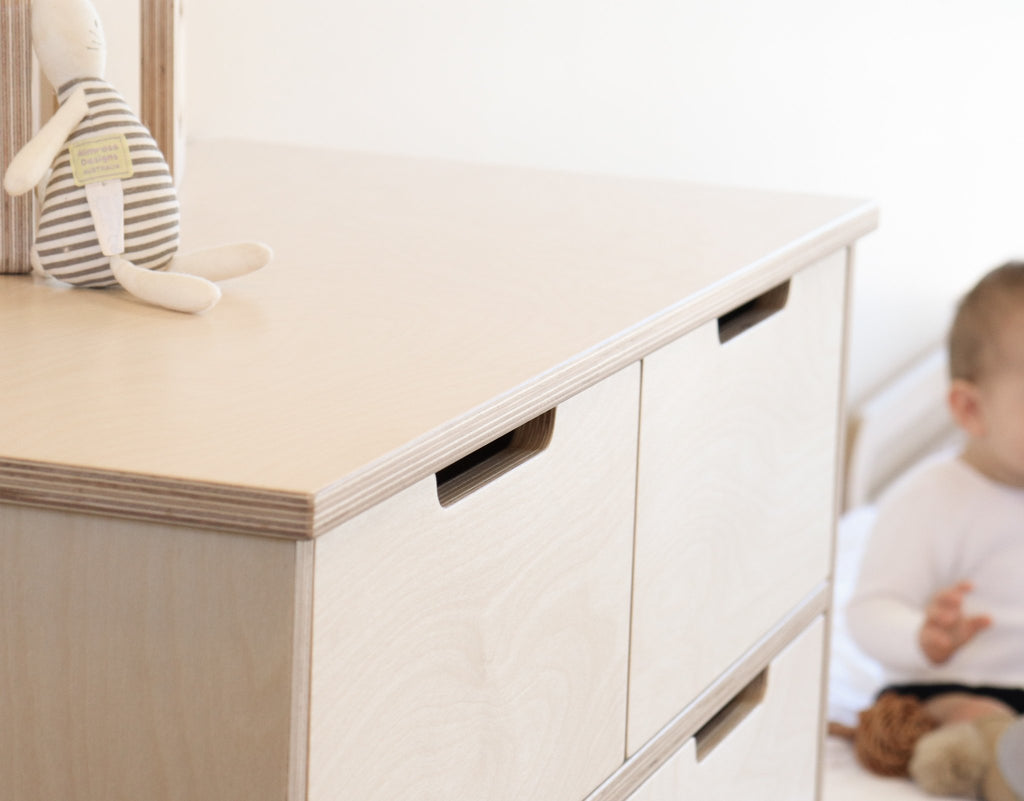 Children's storage drawers with baby in the background