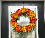 Wreath with Artificial Gold and Orange Flowers Resting on a Bed of Green Grass Succulents