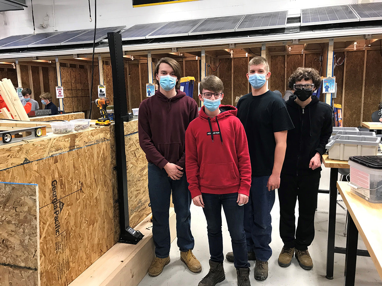 BOCES2 students stand next to the Touchstone SRV TV lift as they work on their custom built cabinet.