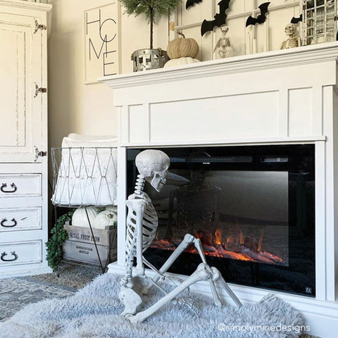 Halloween fun, a skeleton enjoys the warmth of the Forte Electric Fireplace
