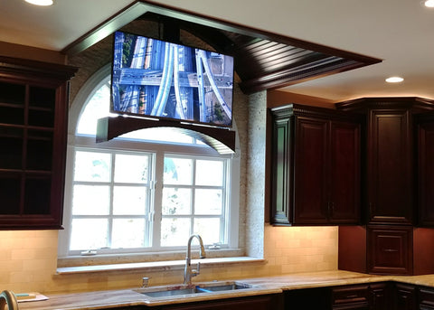 Touchstone Whisper Lift TV lift lowering from the ceiling in front of the kitchen window