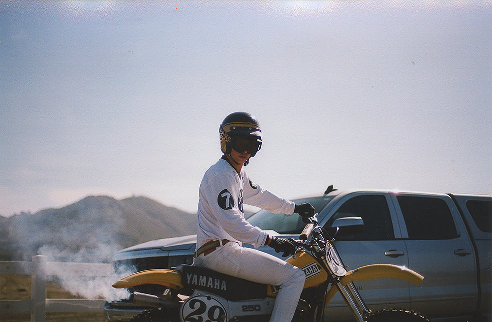 brody mclaughlin sitting on a yellow motorcycle wearing a black bell helmet and von zipper goggles.