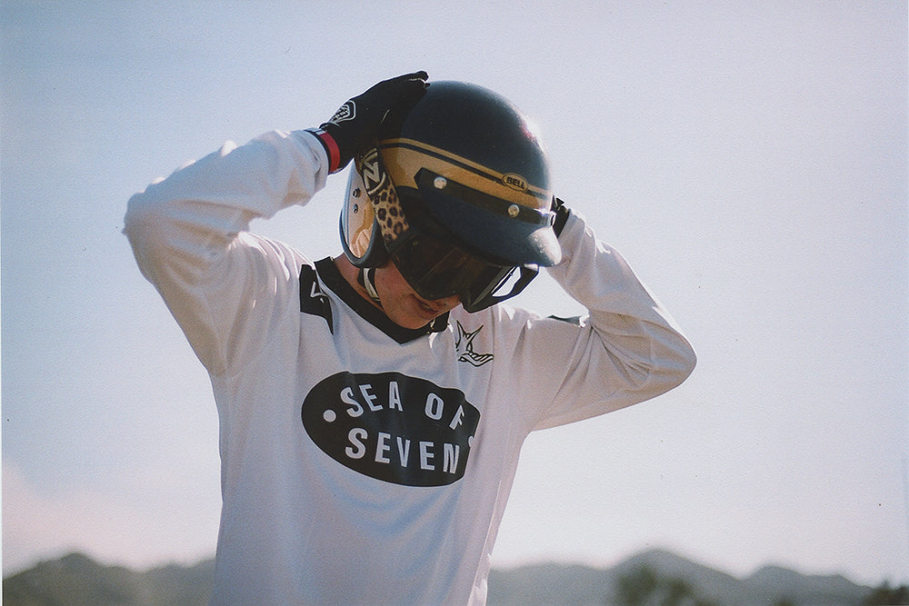 male mx rider putting on a black helmet von zipper racing goggles and sea of seven motocross jersey.