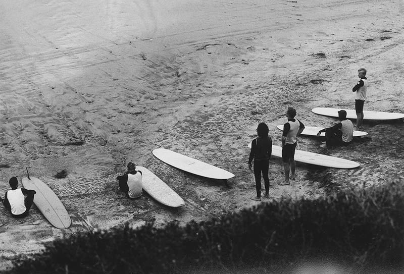 Longboarders in Del Mar line up on the shoreline for their surfing heat.