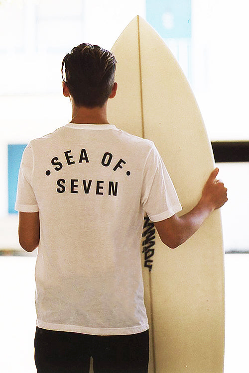 Men holding surfboard wearing Sea Of Seven t-shirt white