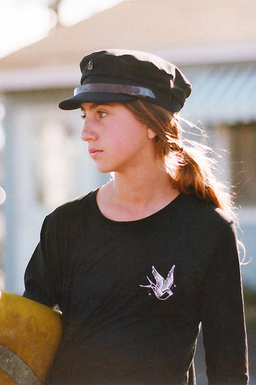 Girl wearing black long sleeve tshirt with a swallow bird and a Fallen Broken Street fiddler cap.