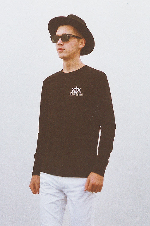 Male model wearing Zara hat Raen sunglasses and Sea Of Seven long sleeve black tee with white h&m pants.