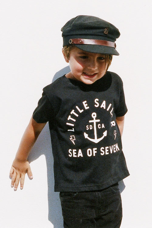 Toddler boy wearing Little Sailor black short sleeve tshirt and fiddler cap by Fallen Broken Street with zara pants.