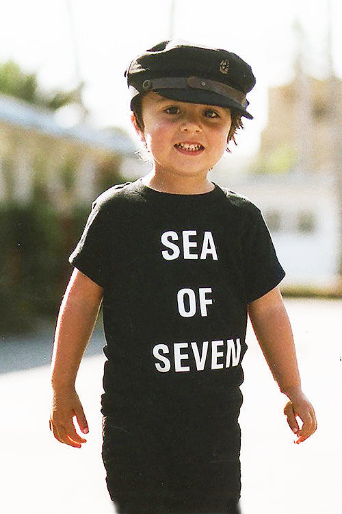Toddler model River English wearing black tee Next Hero by Sea Of Seven with Fallen Broken Street hat and Zara pants with Vans shoes.