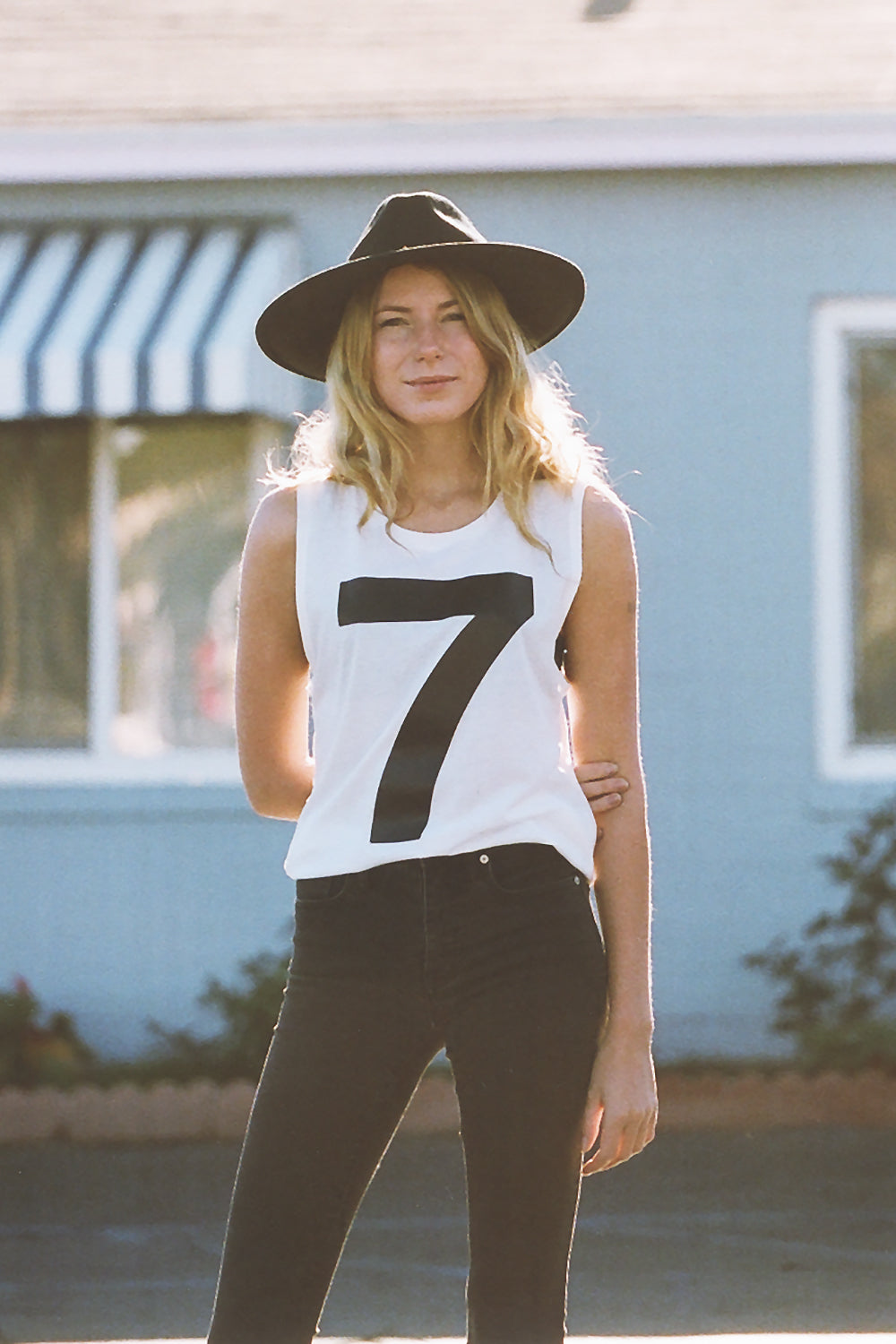 Women's white tank top with a large number seven or a #7 on the front of a white t-shirt wearing brixton hat and vans pants in Oceanside California.