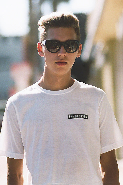 Male model wearing RAEN optics and Sea Of Seven t-shirt.