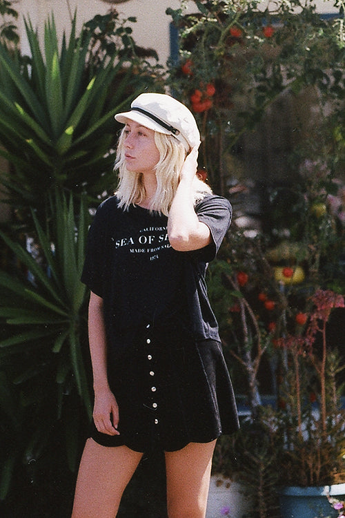 Women's Sending Out An SOS black tee that reads CALIFORNIA SEA OF SEVEN CALIFORNIA 1974 and Brixton hat and Vans black skirt.