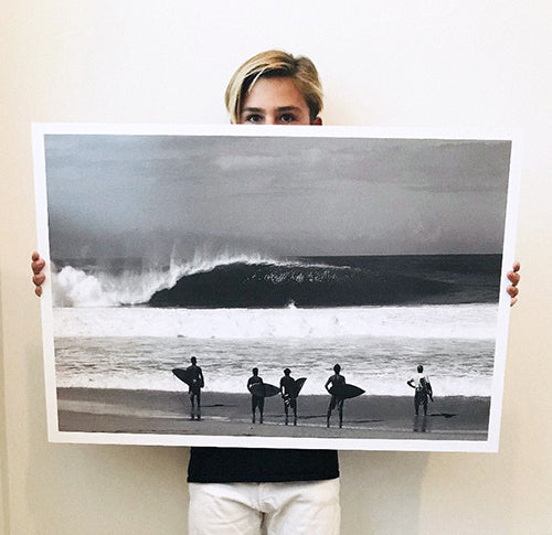 Gavin Mestler holding a surfing posters titled Standing Room Only of a group of surfers on the shoreline at surf spot Pipeline on the North Shore of Oahu in Hawaii.