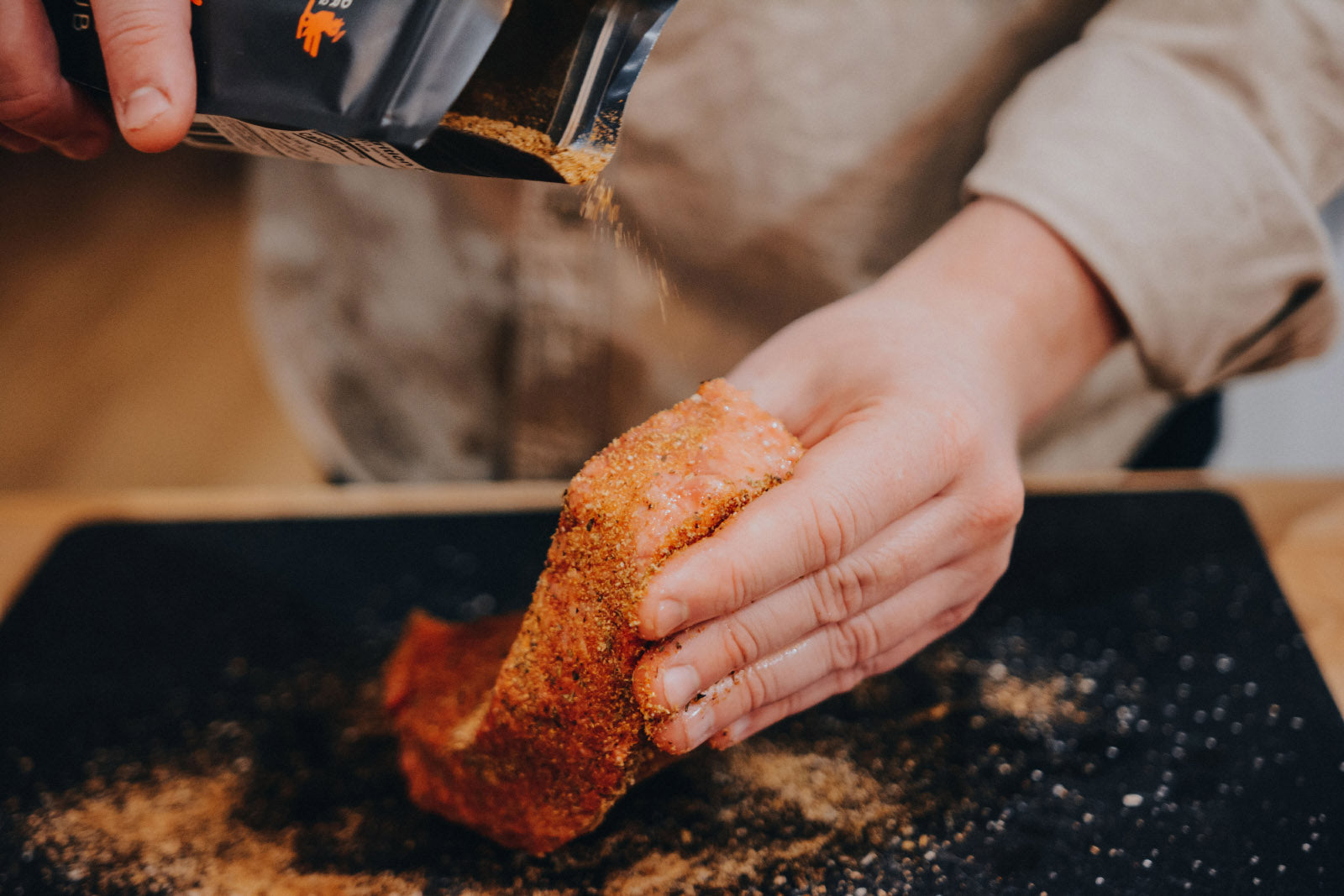 Dry rub seasoning being sprinkled onto a raw steak