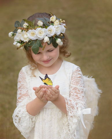 flower girl wearing a garland and playing with a butterfly