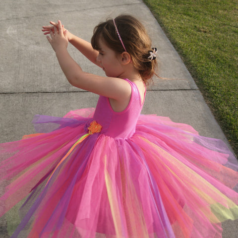 Little girl twirling in pink flower girl dress with tulle