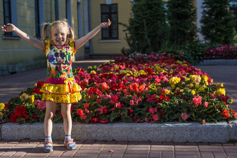 happy little girl standing beside colorful flowers