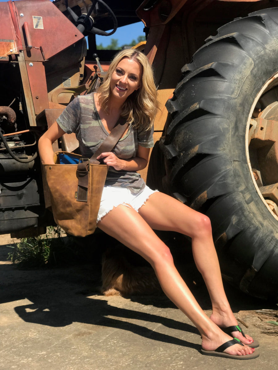 Smiling young woman sitting on a tractor wearing cooks flip flops and holding cook genuine leather burn bag