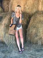 Young woman wearing cooks flip flops leaning on hay bales with cooks genuine leather burn bag draped over her shoulder